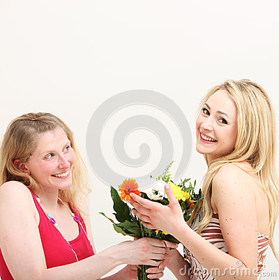 Woman giving her friend a bouquet