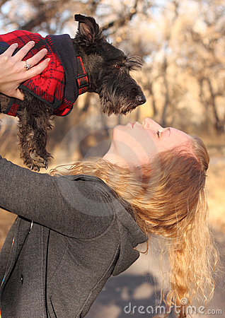 Woman Giving a Kiss to Scottish Terrier Dog