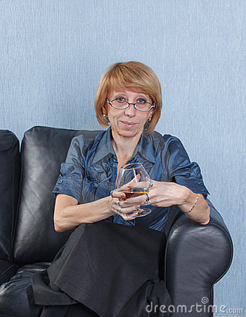 Woman with a glass brandy on couch