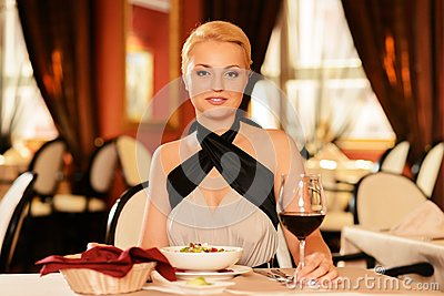 Woman with glass of red wine in restaurant