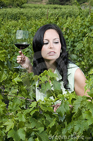 Woman with glass red wine in a Vineyard
