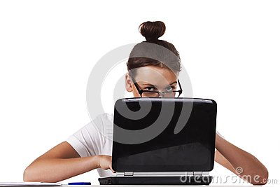 Woman with glasses sits and working on laptop