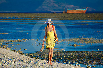 Woman goes for a walk at sundown on the beach