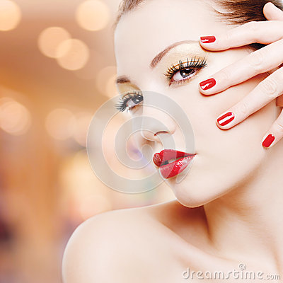 Woman with golden glamour makeup and red manicure
