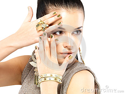 Woman with golden nails and beautiful gold jewelry