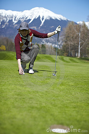 Woman golfer aligning golf ball