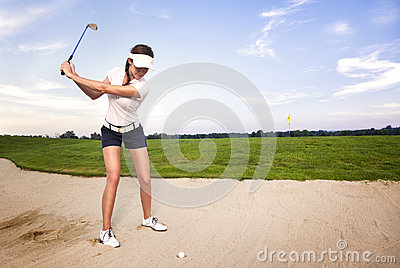 Woman golfer in sand trap preparing to hit ball.