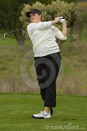 Woman golfer swinging club