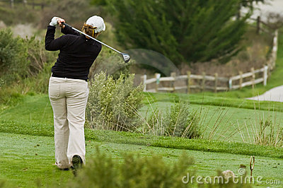 Woman golfer swinging driver on tee box