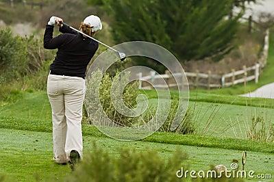 Woman golfer swinging driver on tee box