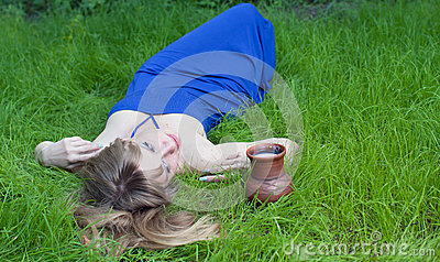 The woman in a grass and a milk jug