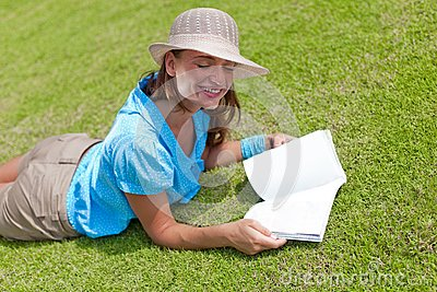 Woman on grass with open book