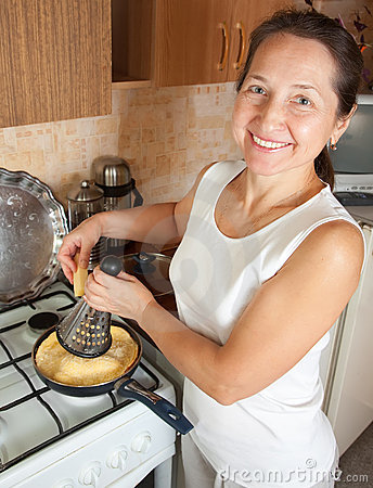 Woman grating cheese into omelette