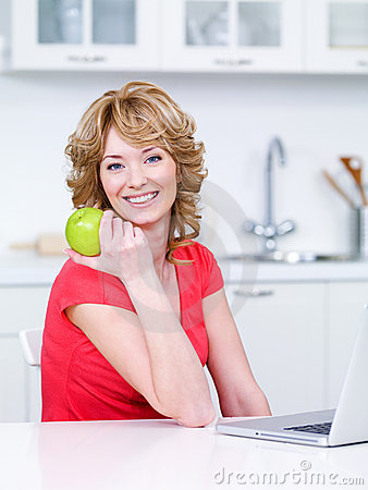 Woman with green apple in the kitchen