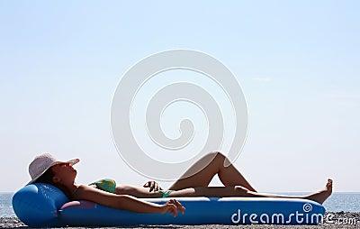 Woman in a green bikini lying on the beach