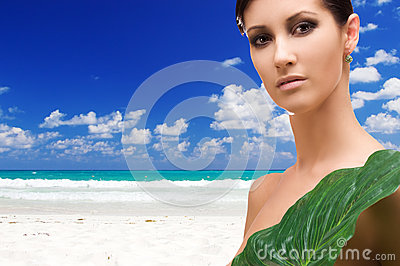 Woman with green leaf on tropical beach