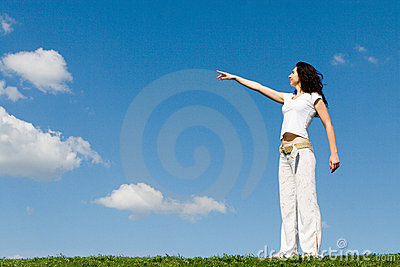 Woman on a green meadow and show something