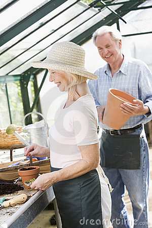 Woman in greenhouse planting seeds and a man