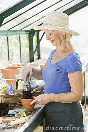 Woman in greenhouse putting soil in pot