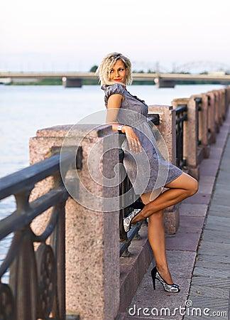 Woman in grey dress on a quay.
