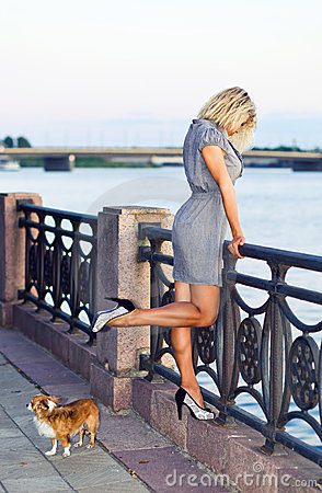 Woman in grey dress on a quay.