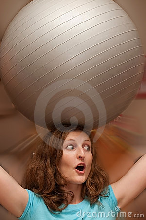 Woman with grey gymnastic ball on head