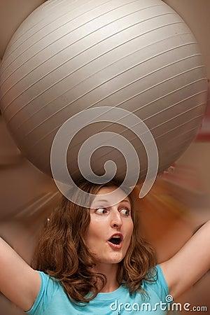 Woman with grey gymnastic ball on head