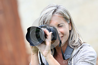 Woman with grey hair using modern camera