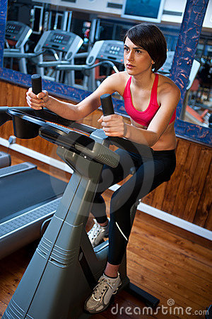 Woman in gym on bycicle