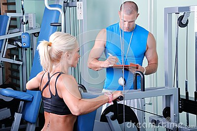 Woman in gym with personal trainer