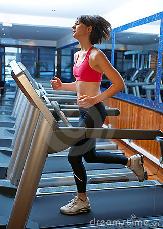 Woman in gym running on track