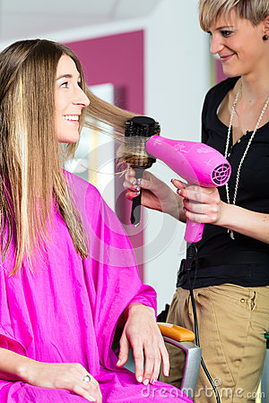 Woman at the hairdresser with blow dryer