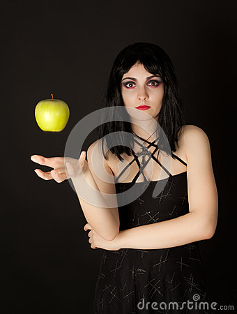 Woman with halloween make up sthrowing green apple
