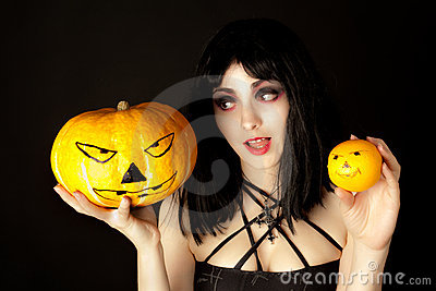 Woman with halloween makeup holding a pumpkin