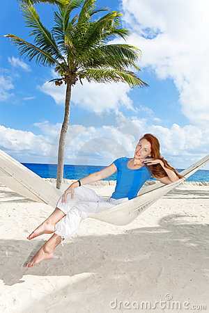 Woman in hammock on background of palm trees