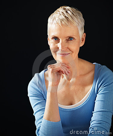 Woman with hand on chin against black background