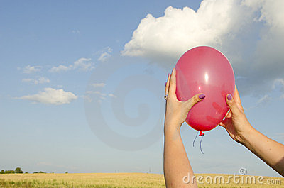 Woman hand hold red balloon background sky field