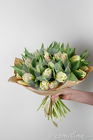Free Woman Hand Holding Soft Yellow Tulips Flowers On White Background. Bouquet Decorated With Kraft Paper Royalty Free Stock Photos - 87351278
