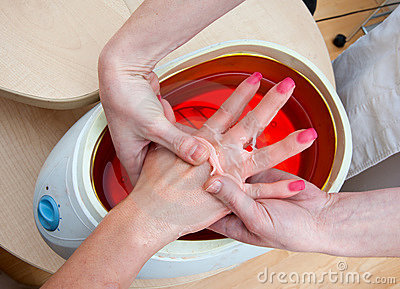 Woman hand in paraffin bath