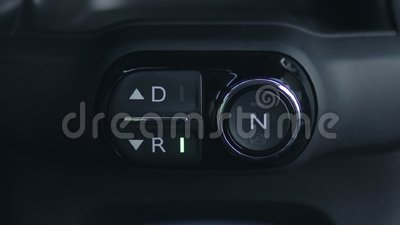 Woman hand pushing reverse gear button in car stock video footage