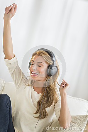 Woman With Hand Raised Enjoying Music Through Headphones