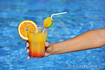 Woman hand with refreshment at swimming pool