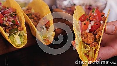Woman hand stuffing hard taco shells - adding the salsa mix stock video