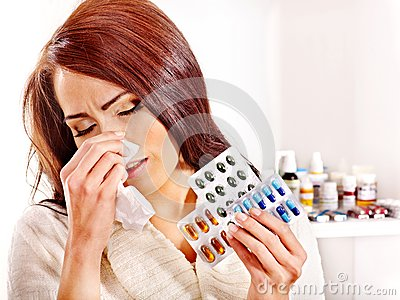 Woman with handkerchief having  tablets and pills.