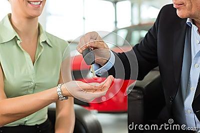 Woman hands car keys to man at auto dealer