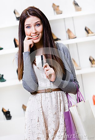 Woman hands credit card in footwear shop