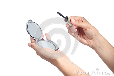 Woman hands holding a hand mirror and a lash mascara ready to make up