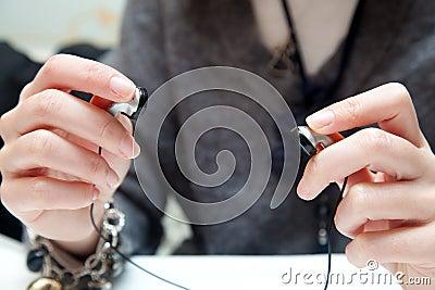 Woman hands preparing in-ear earphones