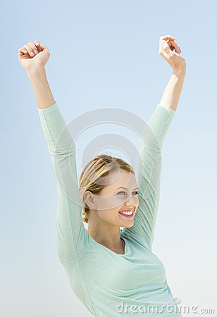 Woman With Hands Raised Looking Away Against Clear Sky