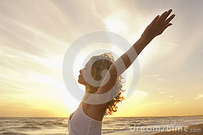 Woman With Hands Raised Meditating At Beach